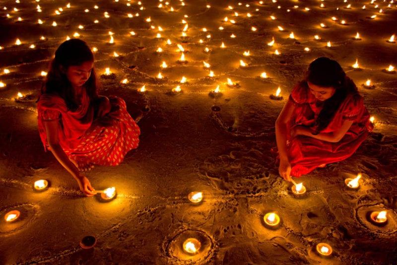 two girls lighting up diya lights for Deepavali