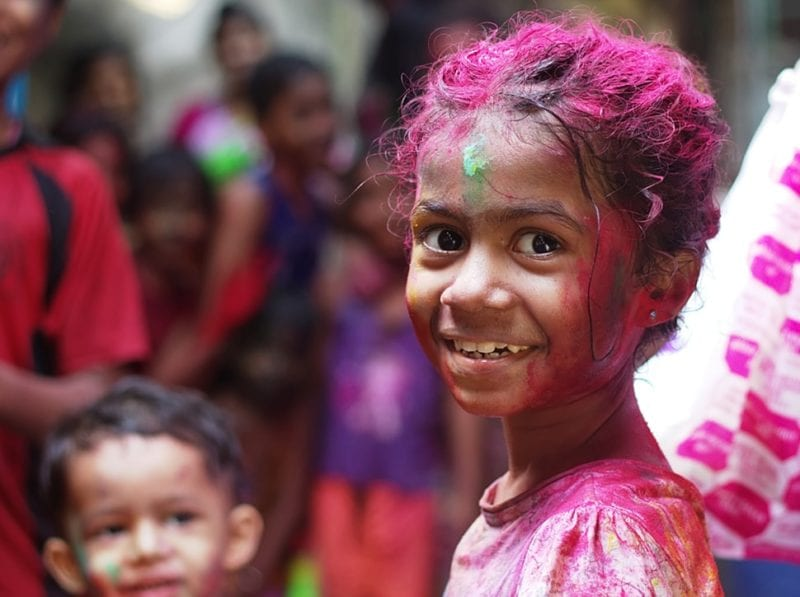 young Indian girl covered in coloured powder smiling