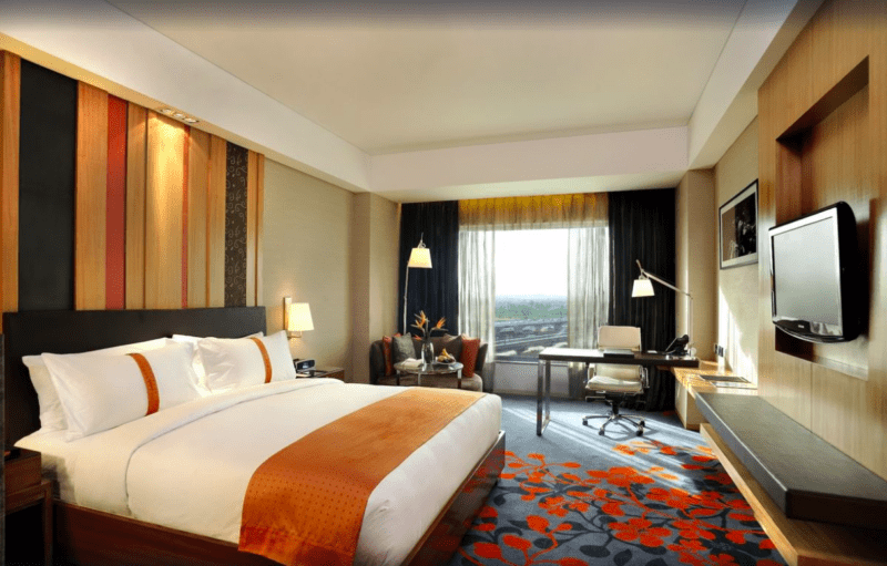 king bed with orange sash in hotel room
