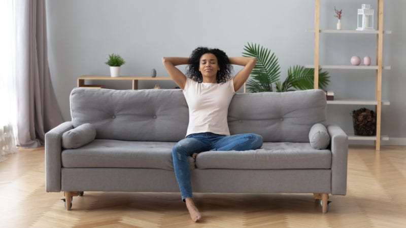 woman wearing white tee and jeans relaxing on sofa