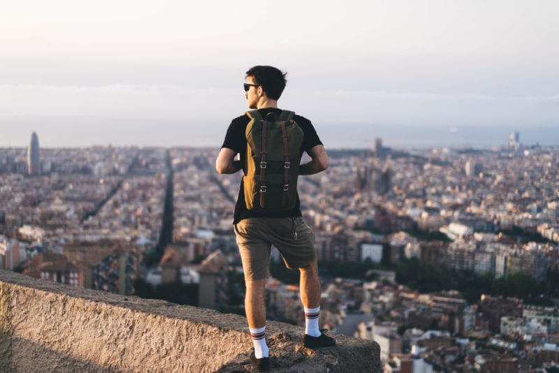 man carrying backpack overlooking a city