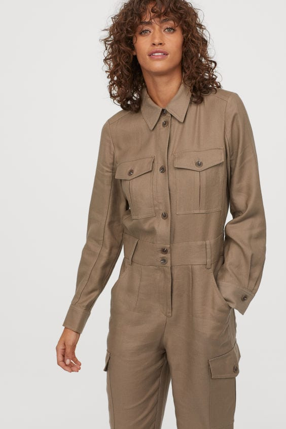 model with curly hair wearing a beige brown boiler jumpsuit