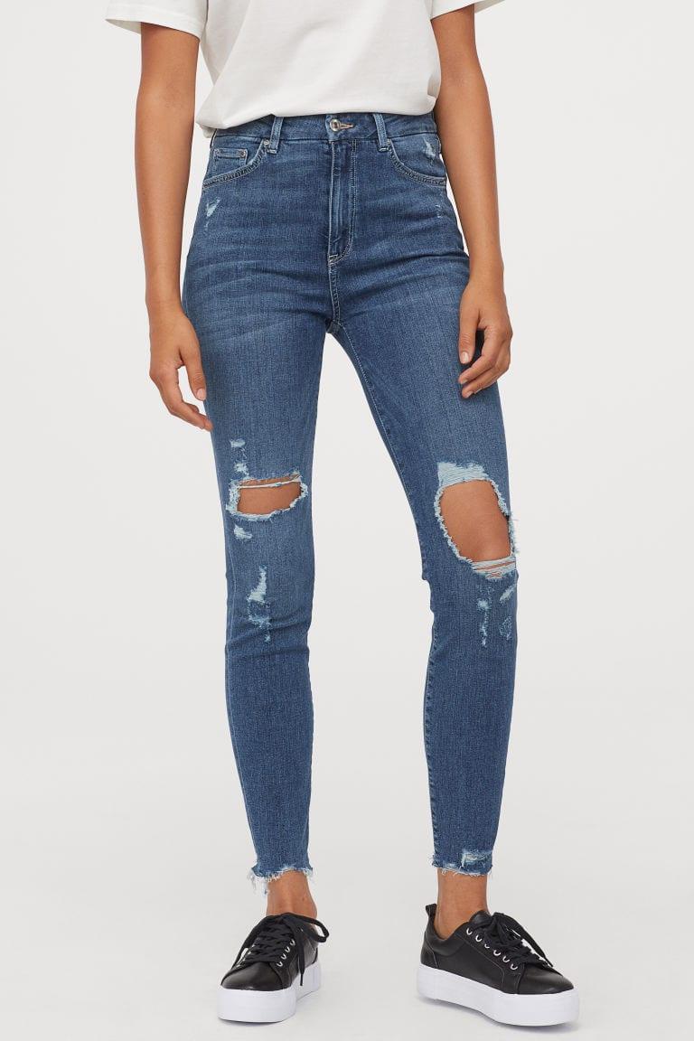model wearing ripped blue jeans