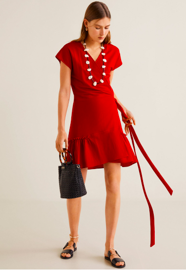 knee length red wrap dress with ruffles paired with black bucket bag and white chunky necklace