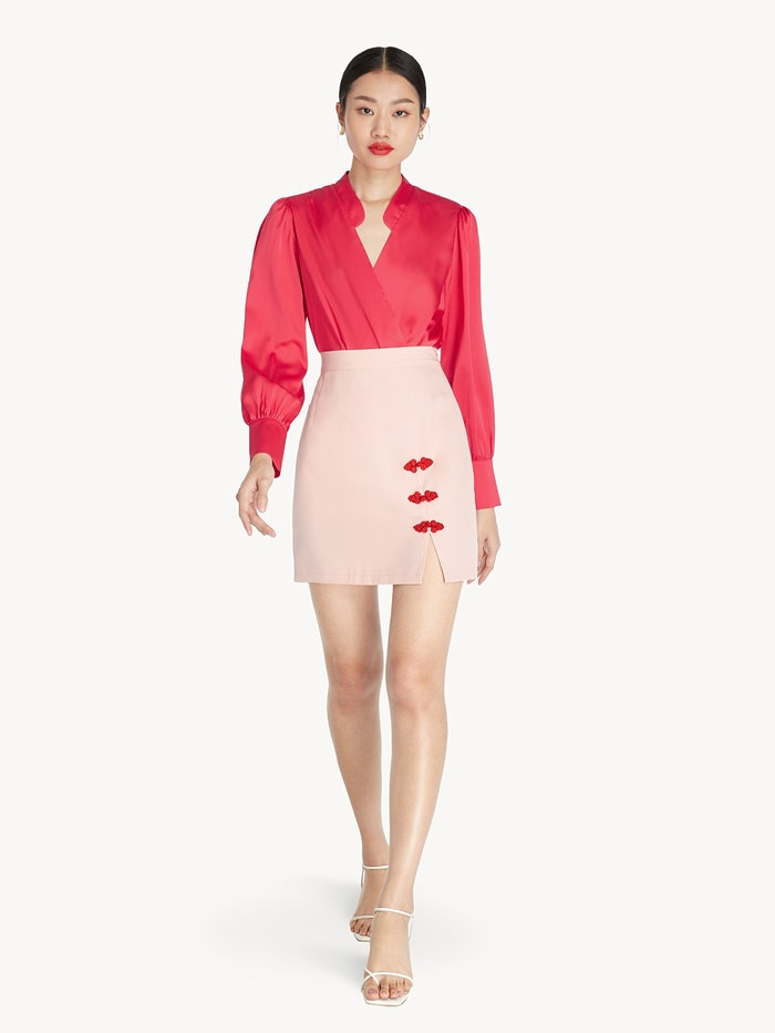 Asian model is hot pink long sleeve top and mini blush pink skirt with frog knots