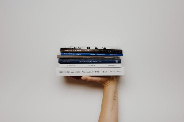 person holding a stack of books